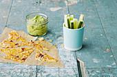 Guacamole mit Crackern und Gurkensticks