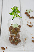 Cinnamon stars with green icing under a glass cloche