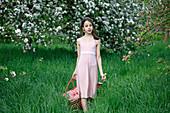 Mädchen läuft mit Picknickkorb auf Wiese unter Apfelbäumen