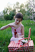 A girl with a juice bottle and basket having picnic in a meadow amongst apple trees