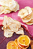 Dried apple, pears and orange slices on strawberry fruit leather