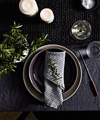 Winterliches Tischgedeck mit Fonduegabel dekoriert mit Rosmarin und Kerzen