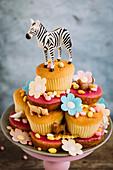 Cupcakes auf Gebäckteller dekoriert mit Tierfiguren, Blüten und Süssigkeiten
