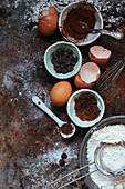 An arrangement of baking utensils: cocoa, chocolate chips, eggs, flour and sugar