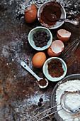 Stillleben mit Backzutaten: Kakao, Schokotropfen, Eier, Mehl und Zucker