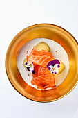 Salmon in buttermilk reduction with potatoes and edible flowers (top view)