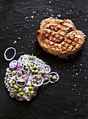 Grilled pork collar steaks with beluga lentils and peas in a yoghurt sauce with red onions