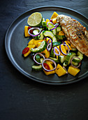 Grilled chicken breast with a cucumber and mango salad