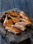 Roast duck, jointed, on a wooden chopping board