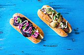 Hot Dog with pork sausage with roast potatoes, a fresh basil pesto and sour cream and with beetroot crisps, mint and beetroot sauce