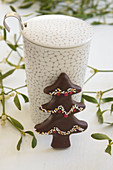 A chocolate-glazed gingerbread Christmas tree with sprinkles against a mug of tea