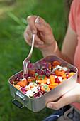 Frau isst Salat mit Radicchio, Karotten und Schafskäse