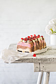 A banana split ice cream cake topped with glace cherries