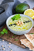 Avocado hummus with chickpeas, black sesame seeds and parsley (Arabia)