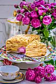 Napoleon-Torte, umgeben von Rosen