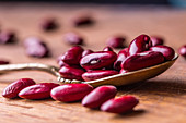 Red beans on a spoon and a wooden surface (close up)