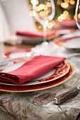 A Christmas place setting with a red napkin