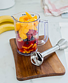 Ingredients for a fruit smoothie in a measuring cup