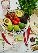Tortillas, avocado, tomatoes, limes, spices and coriander leaves