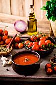 Selbstgemachte Tomatencremesuppe im Schälchen umgeben von Zutaten
