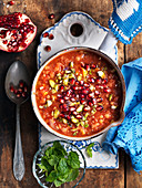 Lentil soup with tomatoes, pistachios, peppermint and pomegranate