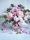 Rosafarbener Blumenstrauß aus Ranunkeln, Kirschblüten und Eukalyptus in einer Vase