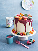 A buttercream cake with colourful macaroons and glaze