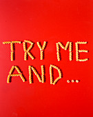 'Try me and...' spelt with fusilli pasta on a red surface