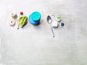 An arrangement of Tupperware, vegetables, spices and a kitchen timer
