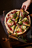 Pizza with ham, goat's cheese and rocket