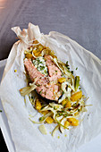 Salmon on a bed of orange fennel on parchment paper