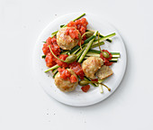 Chicken meatballs on a courgette salad with tomato sauce and caper fruits