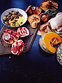 Ingredients for autumnal dishes: pomegranate, olives, mushrooms and pumpkin
