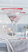 A drink being poured into a Martini glass over a Christmas bonbon