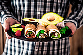 A man holding tray of burritos, avocado and corn on the cob (Mexico)