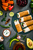 Tortilla wraps with vegetables, surrounded by the ingredients (Mexico)