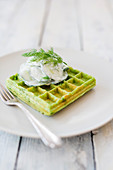 A vegan pea waffle with cucumber yogurt