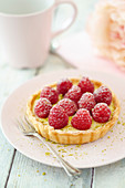 A marzipan tartlet with raspberries and pistachios