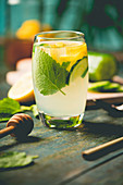 Fresh cool lemon cucumber mint and honey infused water, cocktail, detox drink, lemonade in a glass on wooden background