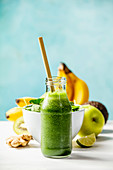 Green smoothie and ingredients on the table against the wall