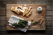 Sliced chicken with thyme on wooden chopping board with scissors and string