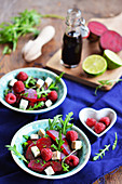 Rocket salad with beetroot, natural tofu and raspberries, with balsamic vinegar and limes in the background
