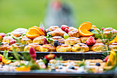 Buffet with cakes, fresh fruits, berries and herb decorations