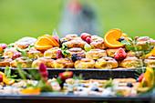 Buffet mit Kleingebäck, dekoriert mit frischen Früchten, Beeren und Kräutern