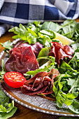 Salatplatte mit Bresaola, Rucola, Babyspinat, Tomaten und Parmesan