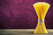 Bunch of spaghetti on wooden table, purple background