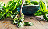 Fresh basil leaves and pesto on wooden table