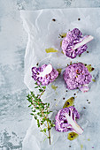 Purple cauliflower with thyme and olive oil on baking paper