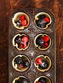 Berry tartlets with sugar in a muffin tin