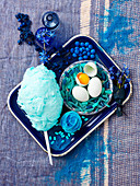 Still life in blue with cotton candy, cupcake and eggs